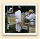 A mechanical lift powered by hydraulics helps these beekeepers handle heavy hive boxes full of honey.